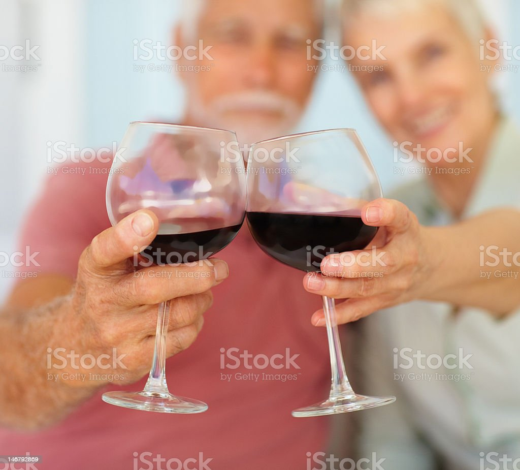 Wineglasses in a senior couple's hands royalty-free stock photo