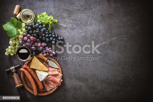 istock Wineglasses with grapes, cheese, ham and corks 695998608