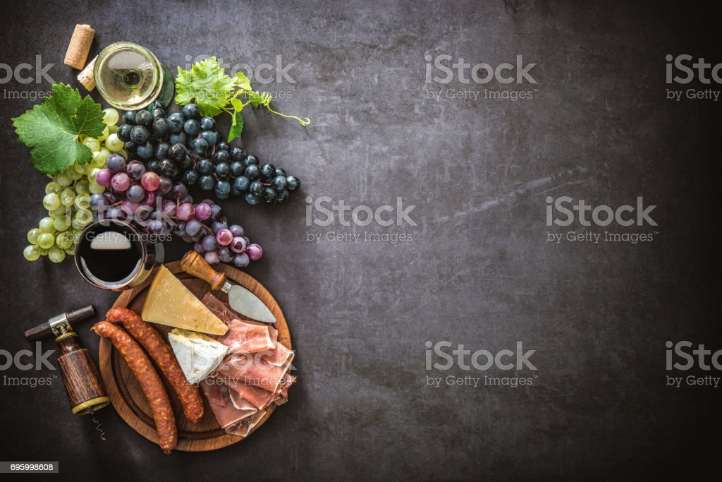 Wineglasses with grapes, cheese, ham and corks stock photo