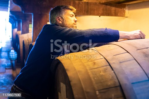 Winemaker working in oak barrels in a cellar winery