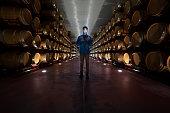 Winemaker working in oak barrels in a cellar winery with tablet pc