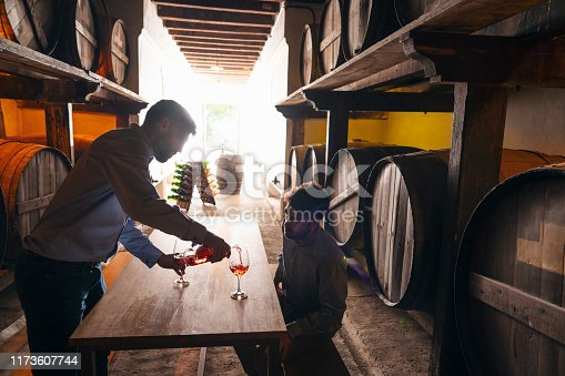 Winemakers wine tasting in oak barrels winery cellar
