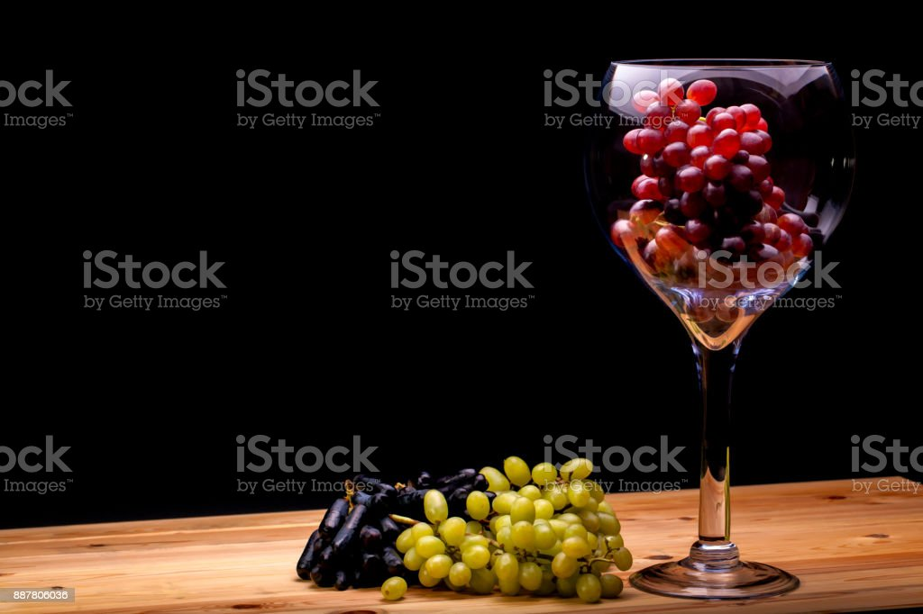 Winemaking. Glass of red wine grapes with green and black bunches. Black background with copy space. stock photo