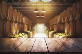 Close up of empty wooden table with blurry wine barrels in the background. Winery and beverage concept. 3D Rendering