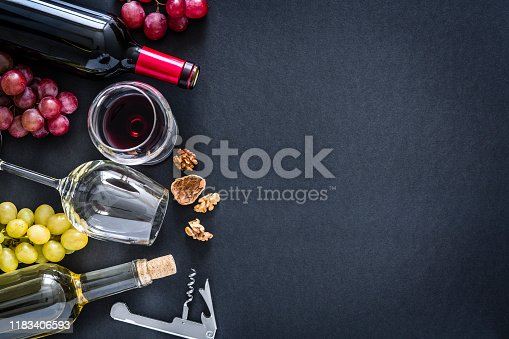 Top view of a black background with a composition of red, rosé and white wine bottles and wineglasses arranged at the left border leaving useful copy space for text and/or logo at the right. Red and white grapes and a vintage corkscrew complete the composition. Predominant colors are red, green and black. XXXL 42Mp studio photo taken with Sony A7rii and Sony FE 90mm f2.8 macro G OSS lens