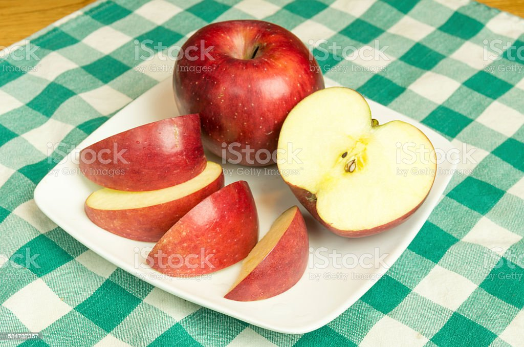 Winesap apple slices on white plate stock photo