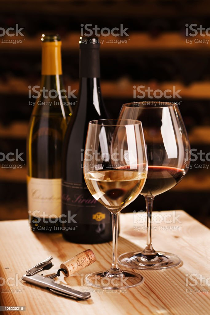 Winetasting in Cellar with Wine Glasses, Bottles, Corkscrew, and Racks royalty-free stock photo