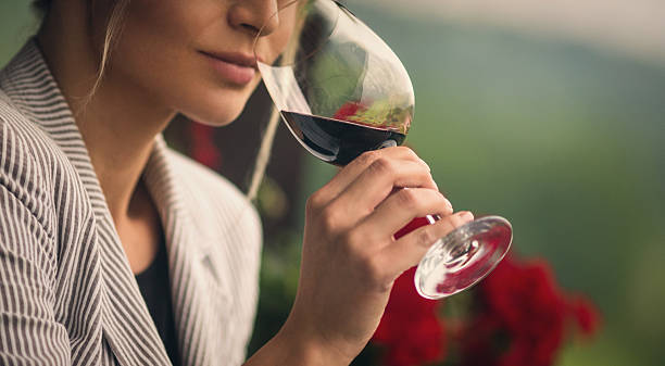 Winetasting. Closeup of unrecognizable adult woman holding a glass of red wine and smelling it before tasting. She's standing outdoors on summer afternoon. Blurry gras and red flowers in background. Toned image. red wine stock pictures, royalty-free photos & images