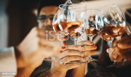 Closeup low angle view of group of unrecognizable people toasting with wine. This toast came after serious winetasting and scrutiny, uploaded soon.