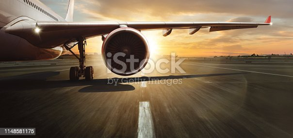 Wing and turbine of commercial jetliner. Modern and fastest mode of transportation. Dramatic sunset sky on background