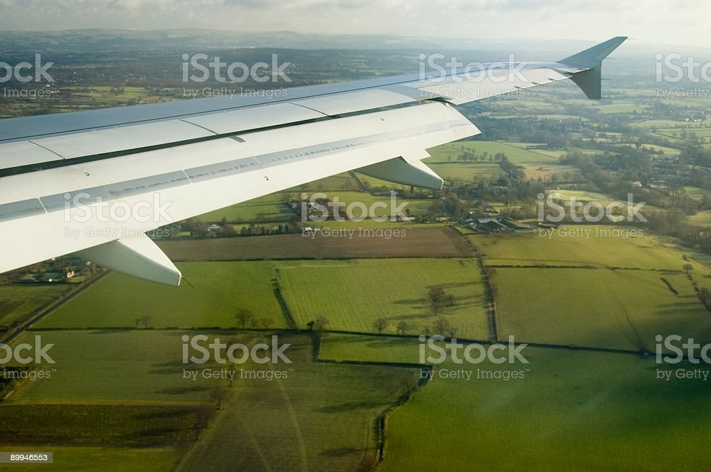 Wing of a Boeing 737 above Englands green fields stock photo