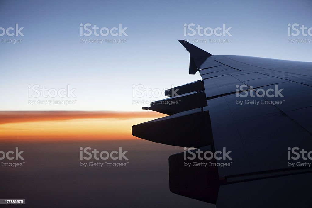 wing of a flying airplane at dusk stock photo