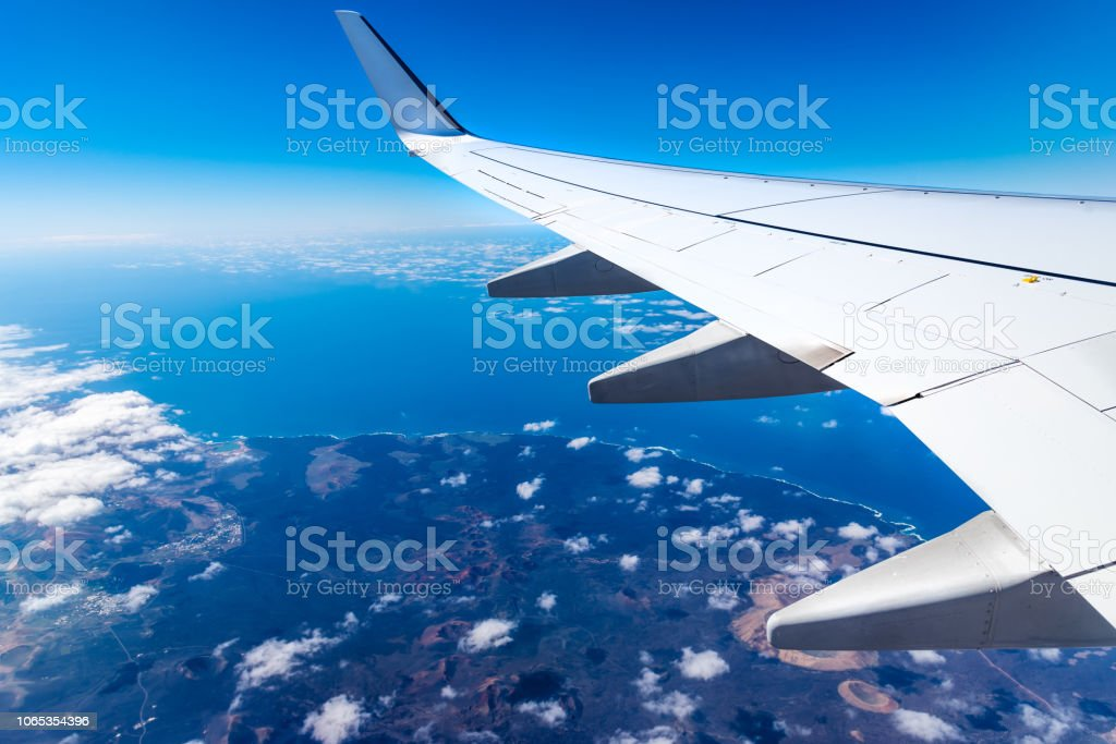 Wing of airplane above island with blue sky stock photo