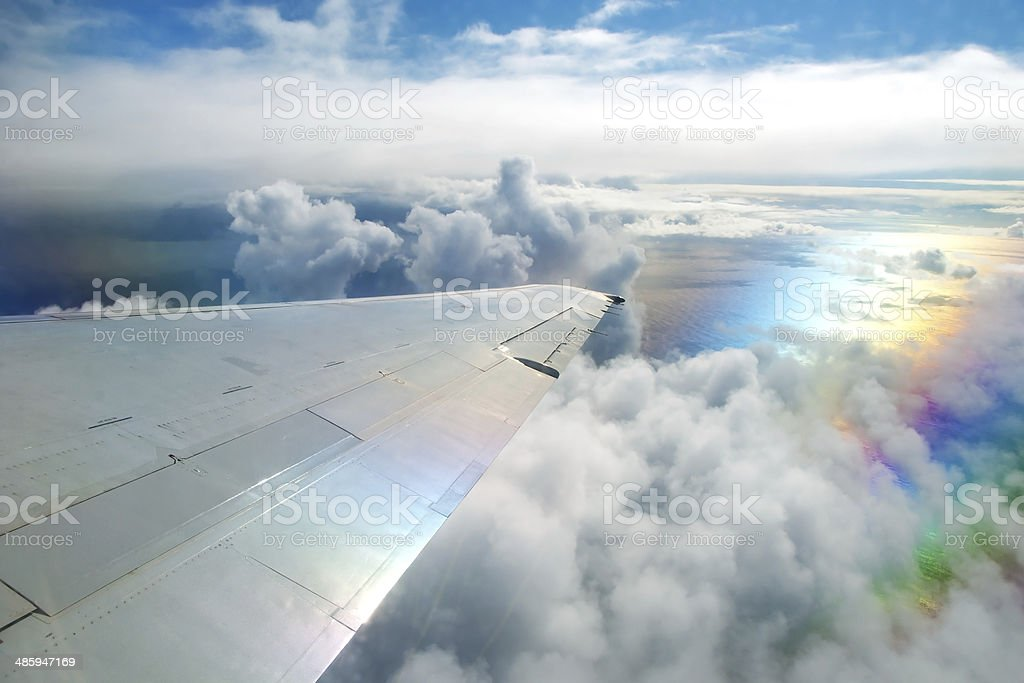 Wing of airplane flying above clouds in sky royalty-free stock photo