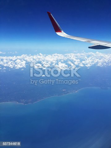 istock Wing of airplane flying above in the sky 537344618