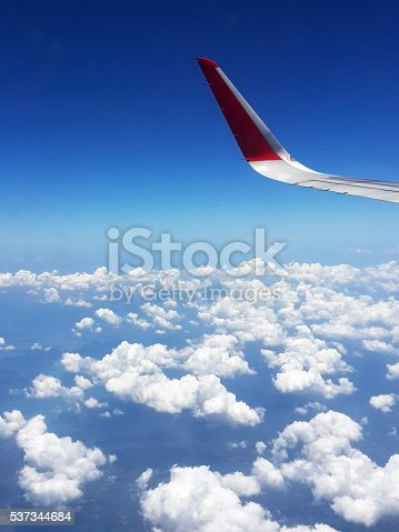 istock Wing of airplane flying above in the sky 537344684