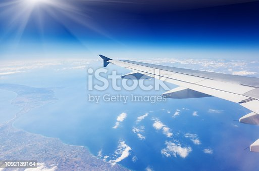 istock Wing of airplane flying above the clouds in the sky 1092139164
