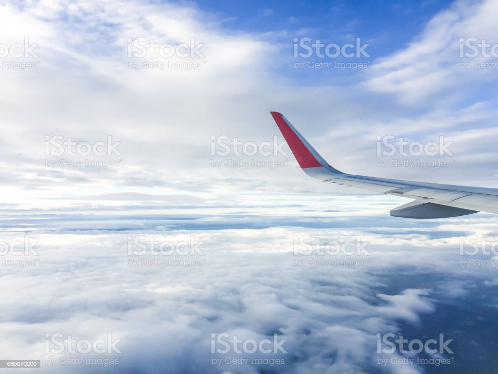 Wing of airplane flying above the clouds in the sky royalty-free stock photo