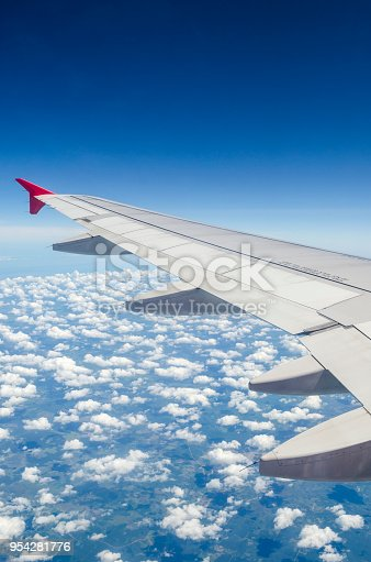 istock Wing of airplane flying above the clouds in the sky 954281776