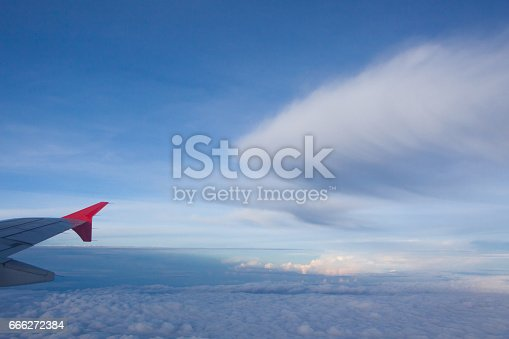 istock Wing of airplane flying above the clouds . 666272384