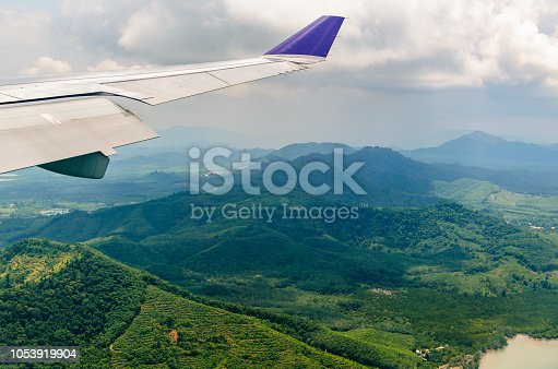 621114928istockphoto Wing of airplane flying in cloudy sky over the green mountains. 1053919904