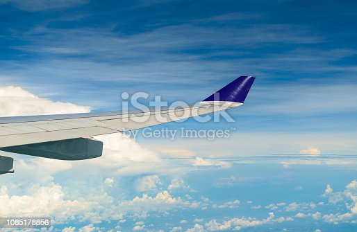 621114928istockphoto Wing of airplane flying over the  cloudy sky. 1085178856