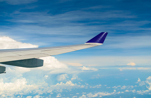 621114928 istock photo Wing of airplane flying over the  cloudy sky. 1085178856