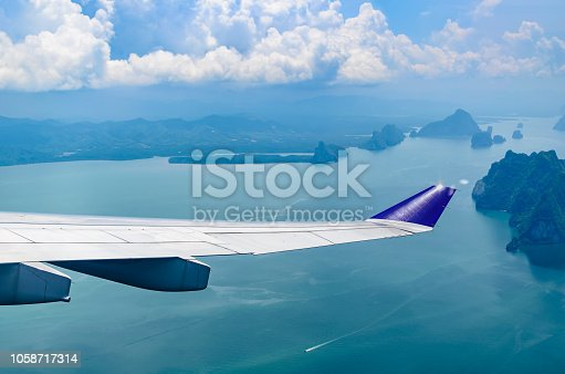 621114928istockphoto Wing of airplane flying over the sea with cloudy sky. 1058717314