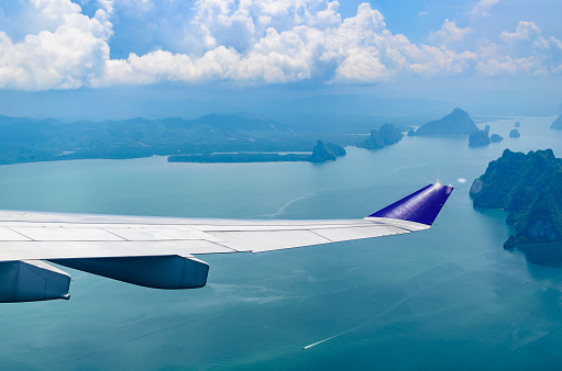 621114928 istock photo Wing of airplane flying over the sea with cloudy sky. 1058717314