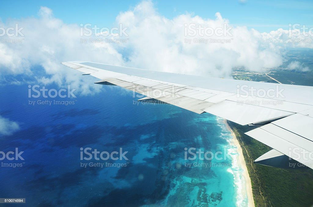 Wing of an airplane flying above the clouds over island stock photo