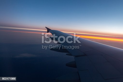 484616224 istock photo Wing of an airplane flying above the clouds 802471986