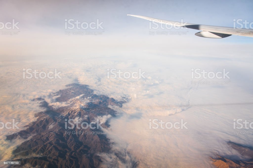 Wing of an airplane flying above the clouds with blue sky. View at...