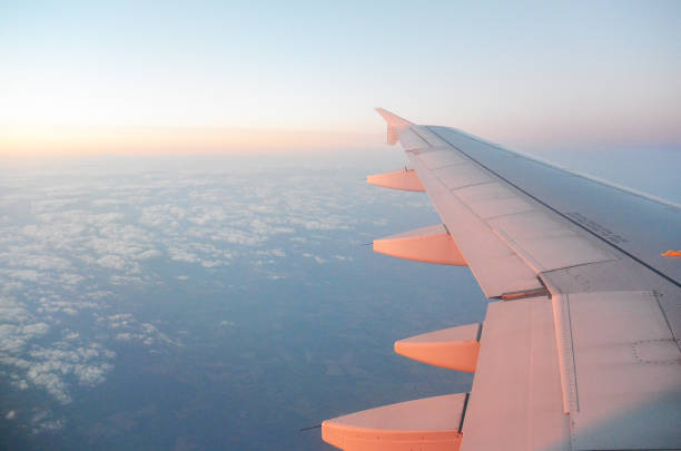 Wing of an airplane flying above the sunrise clouds stock photo