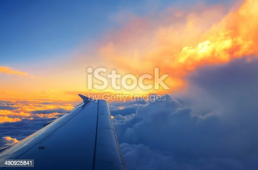 902818356 istock photo Wing of an airplane flying above the sunset clouds 490925841