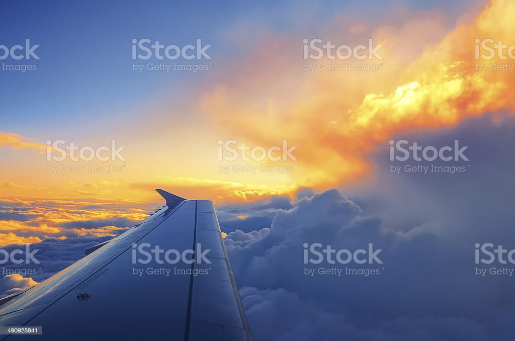 Wing of an airplane flying above the sunset clouds stock photo
