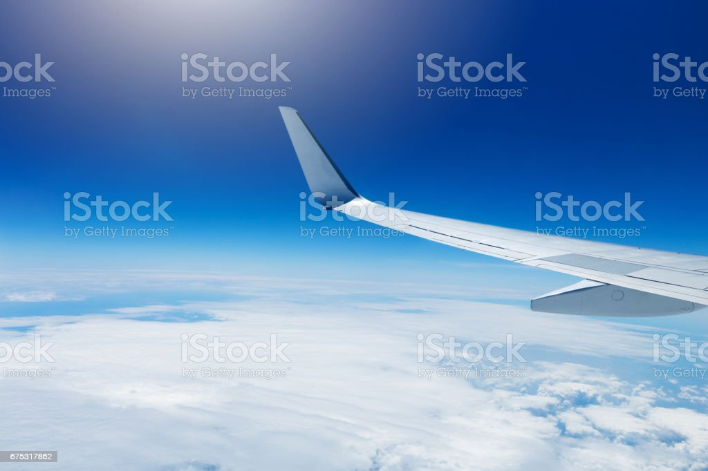 wing of an airplane flying high in the sky above the clouds stock photo