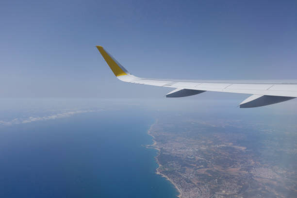 wing of an airplane flying - aviation and environment summit stock photos and pictures