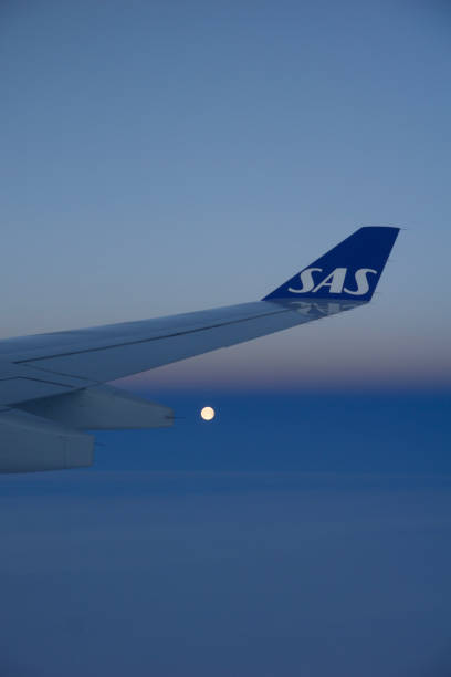 Wing of an airplane over blue sky with the moon in the background stock photo