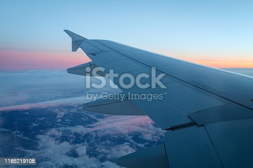 902818356 istock photo wing of an airplane through the window at sunset 1185219108