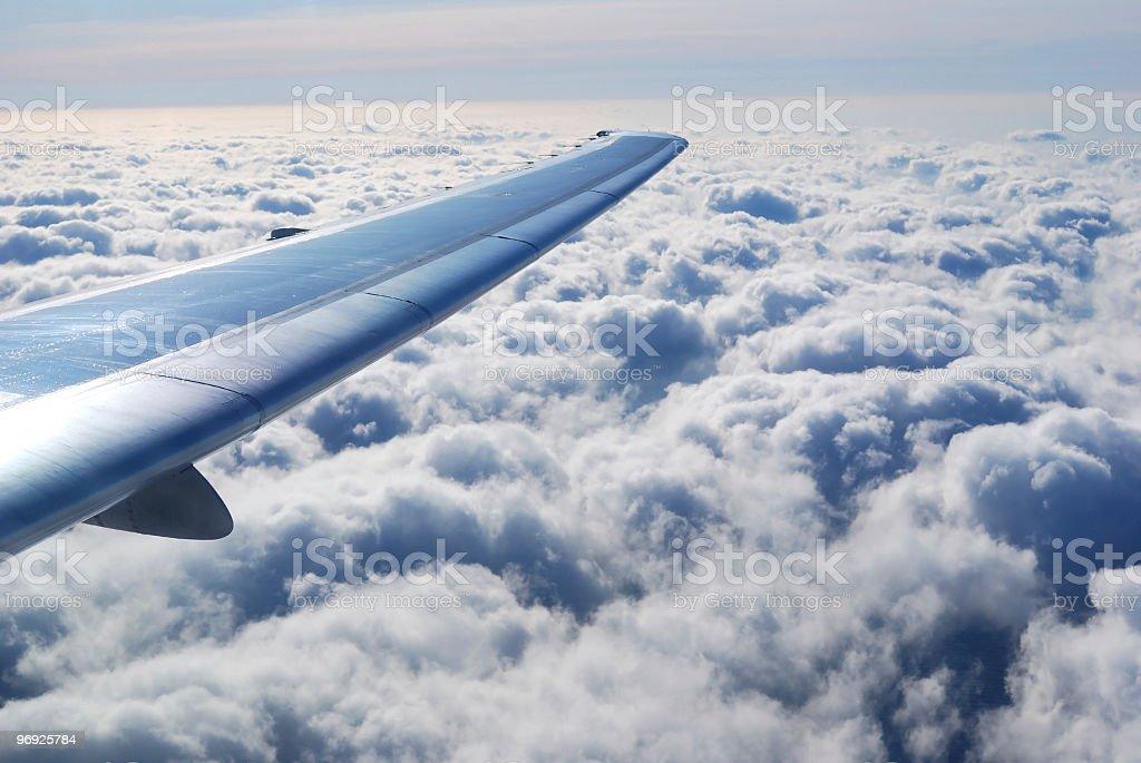 Wing of Commercial Airplane Above Heavy Cumulus Clouds royalty-free stock photo