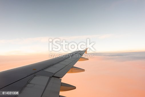 621114928istockphoto Wing of the airplane on blue and pink sky background 614031008