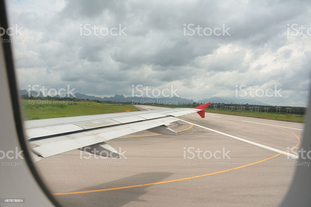 Wing view and taxi way before takeoff On cloudy days stock photo