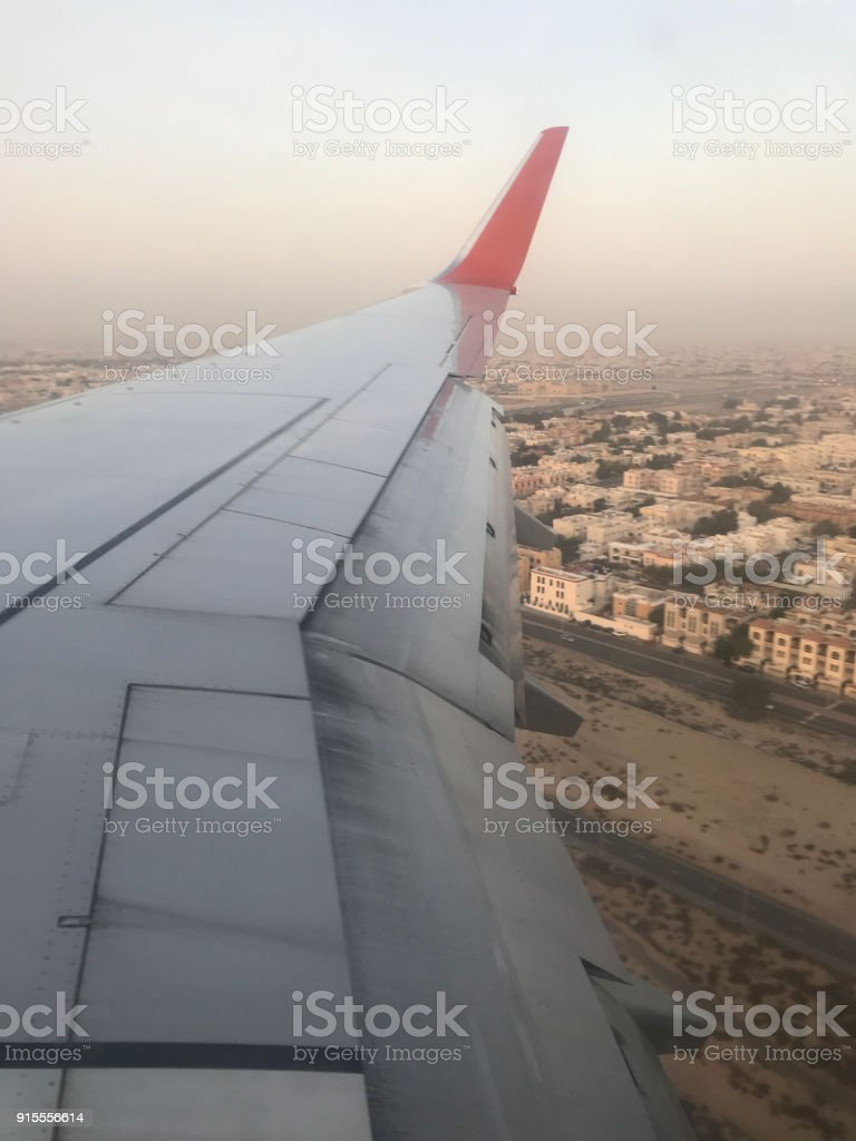 Wing view of civil passenger aiplane over the city. stock photo