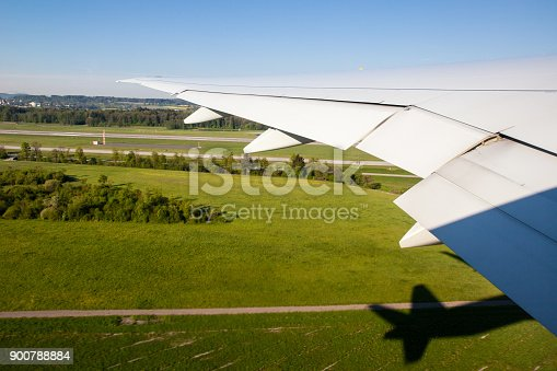 900763322 istock photo Wing view of Take-off as a passenger with shadow 900788884