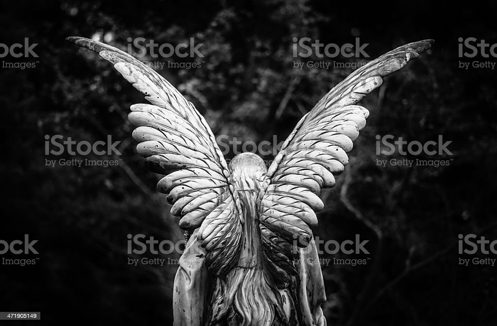 Winged angel gravestone back view stock photo