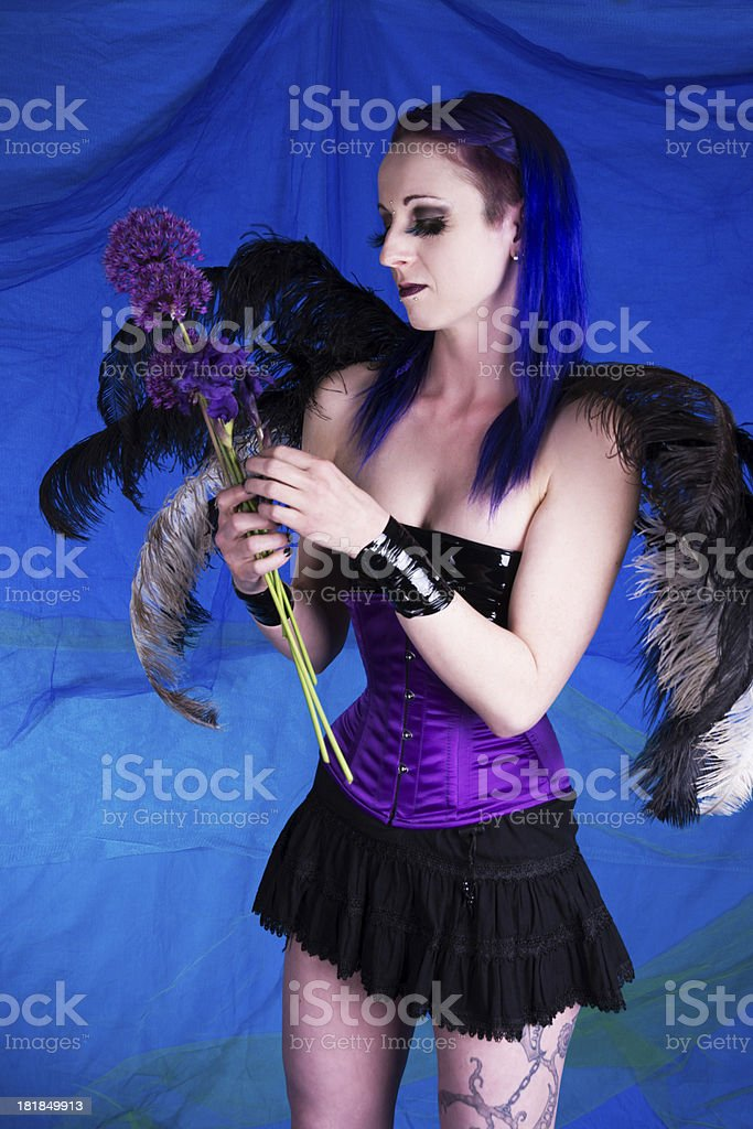 Winged woman adjusting flowers. stock photo