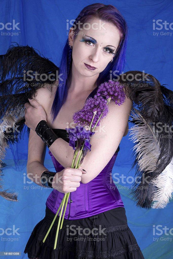 Winged woman holding purple flowers in studio. stock photo