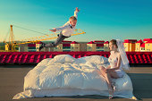 Happy groom flying on bed to his sweetheart on the roof of house in sunrise
