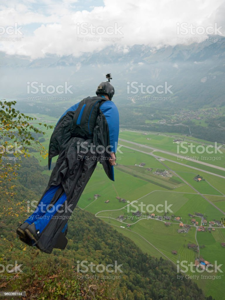 Wingsuit flyer descends into mountain valley stock photo