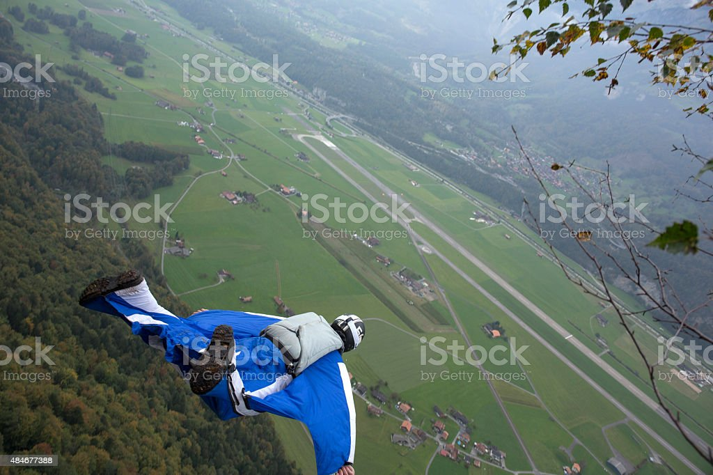 Wingsuit jumper launches out from cliff, valley below stock photo